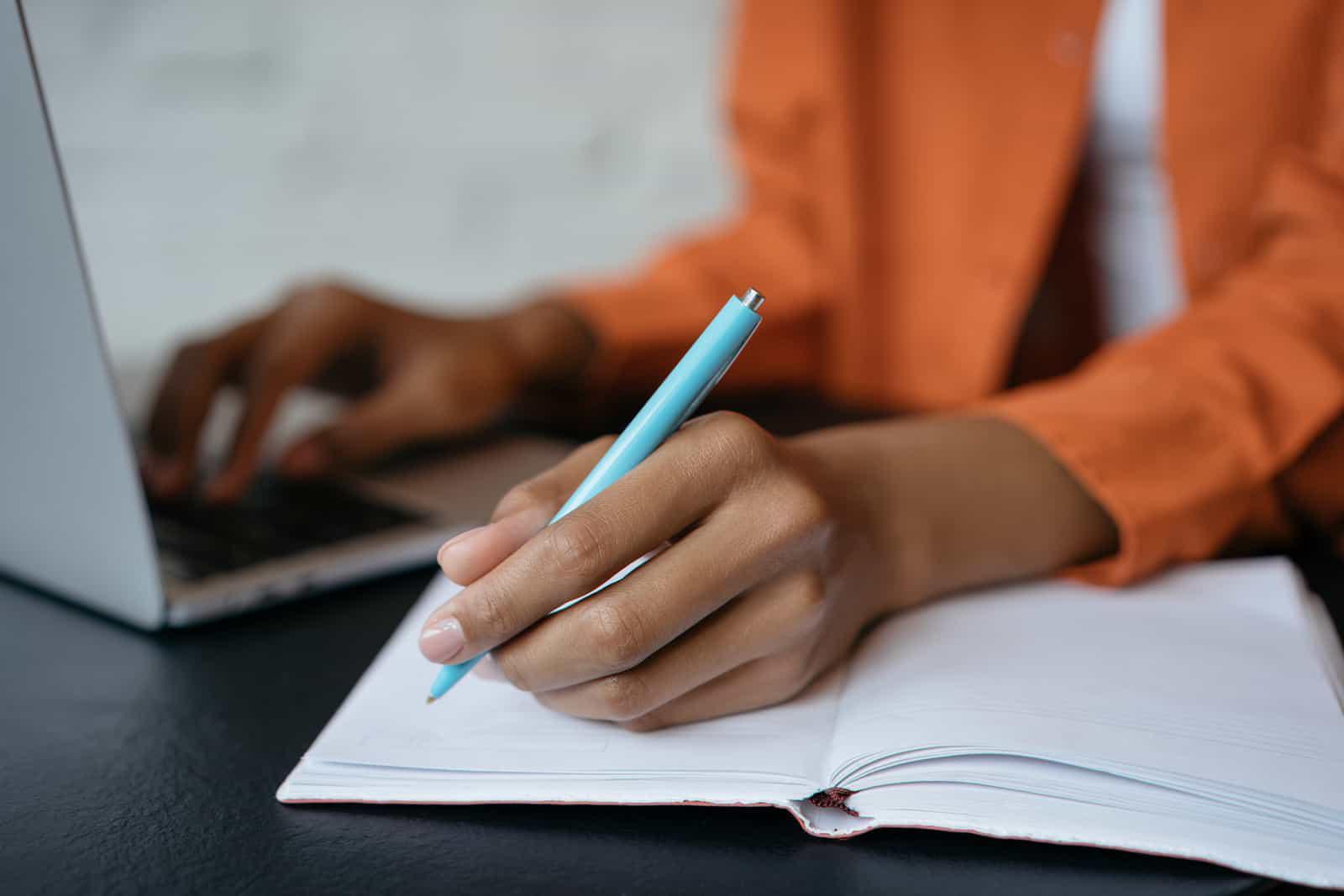 特写镜头中,学生手握笔,在笔记本上写字,在家里工作. 电子学习